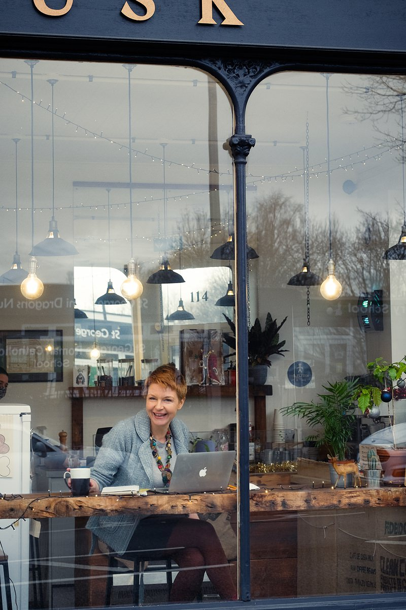 gayle-johnson-laughing-and-writing-in-coffee-shop